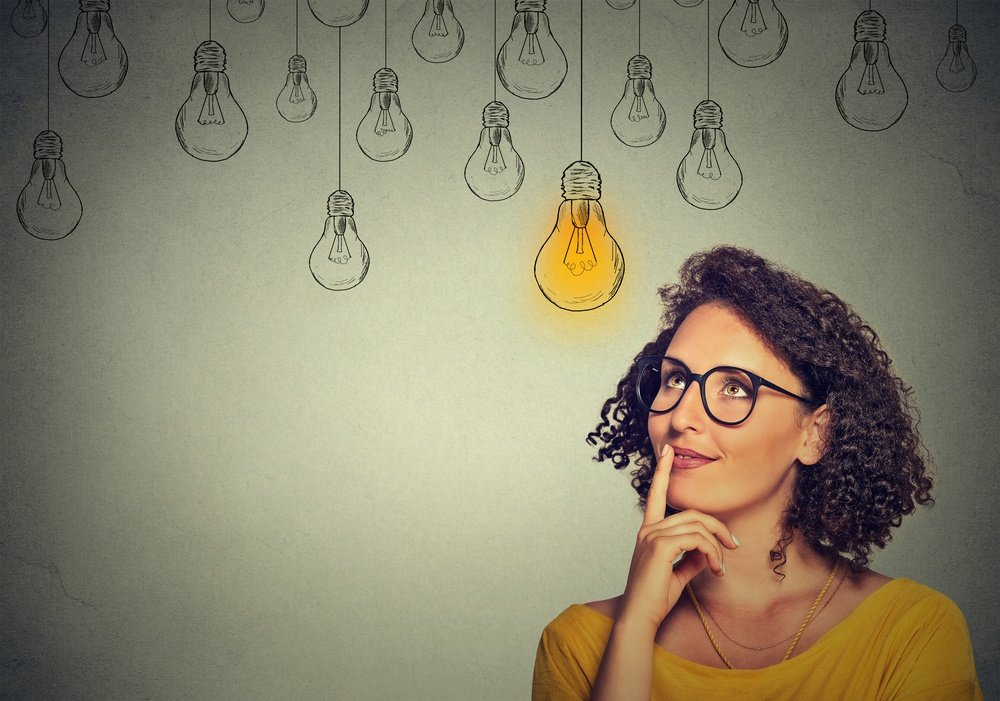 Thinking woman in glasses looking up with light idea bulb above head isolated on gray wall background.jpeg
