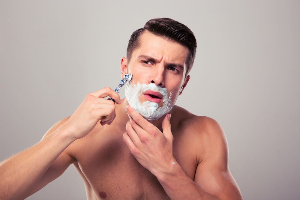 Young man shaving with foam and razor over gray background